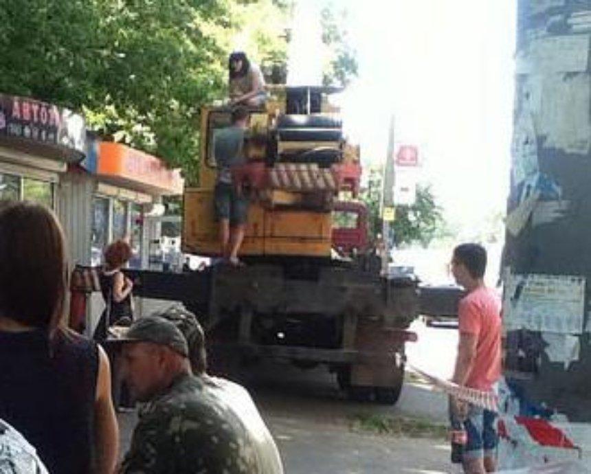 В Киеве владелица МАФа вылезла на автокран и грозится порезать вены (фото)